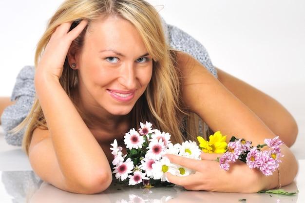 Ritratto di una bella giovane donna bionda sexy in posa in studio in un mini abito con fiori su una scena bianca