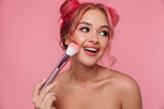 Ritratto di bella donna senza camicia con acconciatura colorata che applica cosmetici con pennello per il trucco