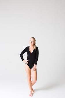 Ritratto di un bellissimo modello sottile in tuta nera
