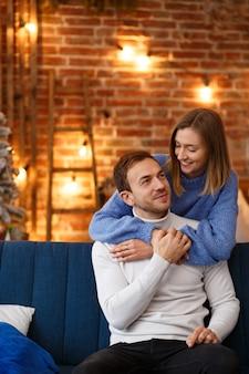Ritratto di belle coppie sorridenti che abbracciano a natale