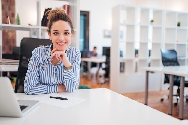 Ritratto di un bello impiegato di concetto femminile sorridente che si siede nel luogo di lavoro.
