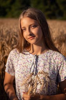 Ritratto di bella ragazza sorridente che tiene alcune orecchie di segale seduto per terra nel campo di grano maturo. ragazza attraente in vestito