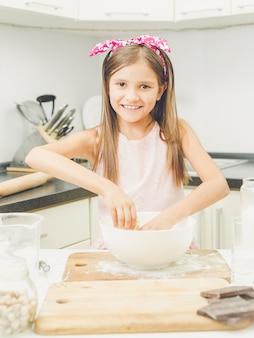 Ritratto di bella ragazza sorridente che fa l'impasto per la torta in una ciotola bianca