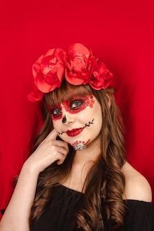 Ritratto di una bella ragazza sorridente con il trucco dia de los muertos con sfondo rosso.