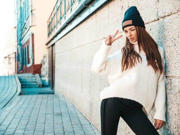 Ritratto di bella modella sorridente. donna vestita di caldo maglione bianco hipster e berretto. in posa per strada