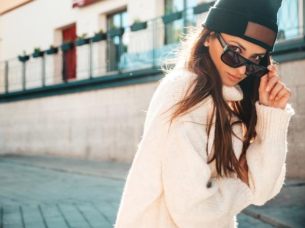 Ritratto di bella modella sorridente. donna vestita di caldo maglione bianco hipster e berretto. donna alla moda in posa per strada