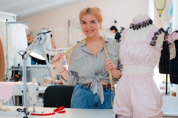 Ritratto di una bella sarta sorridente con un metro a nastro in piedi accanto a un manichino in abiti firmati in uno studio di sartoria