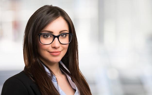 Ritratto di una bella donna sorridente che tiene i suoi occhiali