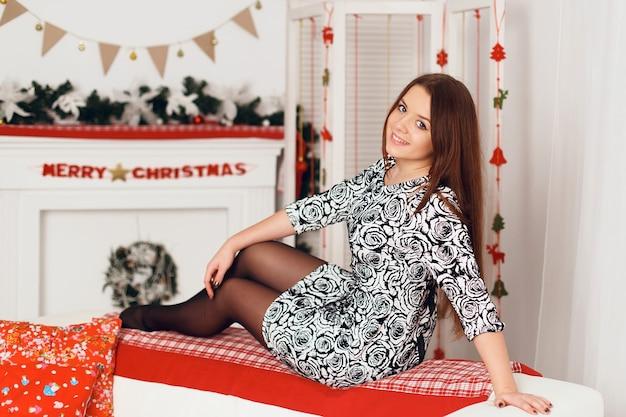 Ritratto di una bella donna adolescente sorridente seduta sul retro del divano