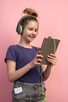 Ritratto di una bella ragazza adolescente sorridente in cuffie e un tablet nelle sue mani