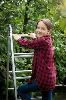 Ritratto di bella ragazza sorridente in camicia a scacchi rossa salendo la scaletta in giardino