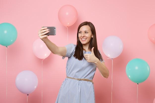 Ritratto di bella donna sorridente in vestito blu che fa selfie sul telefono cellulare che mostra pollice in su su sfondo rosa con mongolfiere colorate. festa di compleanno, concetto di emozioni sincere della gente.