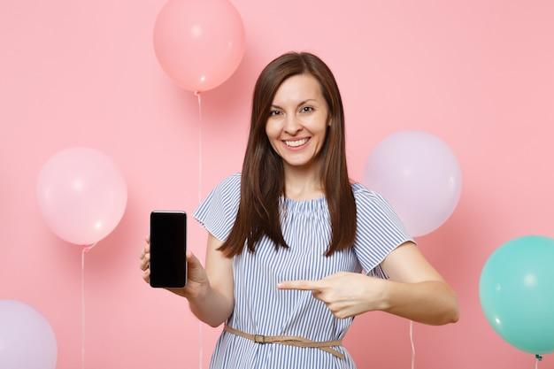 Ritratto di bella donna sorridente in vestito blu che tiene il dito indice puntato sul telefono cellulare con schermo vuoto vuoto su sfondo rosa con mongolfiere colorate. concetto di festa di compleanno.