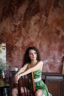 Ritratto di una bella donna sorridente di aspetto europeo in un vestito con capelli ricci. moda e bellezza