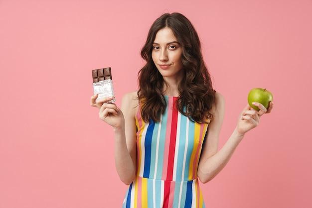Ritratto di bella donna sorridente che posa isolata sopra la parete rosa che tiene mela e cioccolato