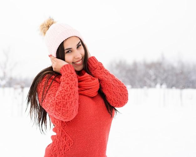 Ritratto di una bella donna sorridente in maglione rosso e cappello nel parco innevato