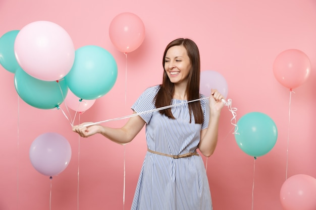 Ritratto di bella donna sorridente che indossa un abito a righe blu che guarda da parte tenendo palloncini d'aria colorati su sfondo rosa di tendenza brillante. festa di compleanno, concetto di emozioni sincere della gente.
