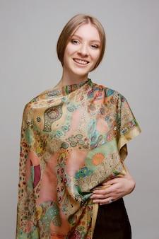 Ritratto di bella donna sorridente con scialle di seta colorata