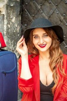 Ritratto di una bellissima giovane donna caucasica sorridente con un cappello nero con bagagli seduto nell'antico edificio che guarda la telecamera all'aperto