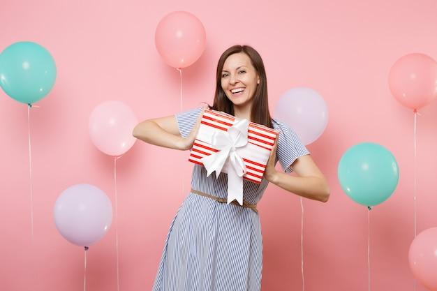 Ritratto di bella giovane donna sorridente in abito blu che tiene scatola rossa con regalo presente su sfondo rosa pastello con mongolfiere colorate. festa di compleanno, concetto di emozioni sincere della gente.