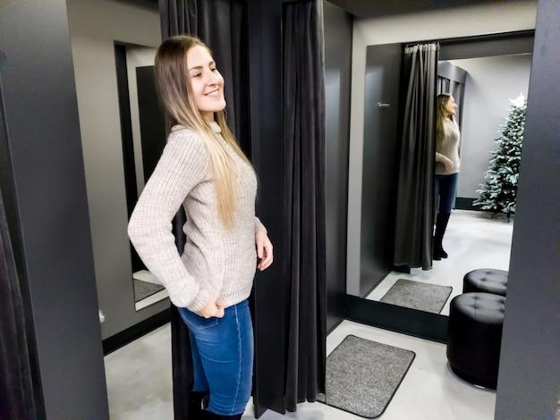 Ritratto di bella giovane donna sorridente che prova un maglione di lana caldo nello spogliatoio del centro commerciale