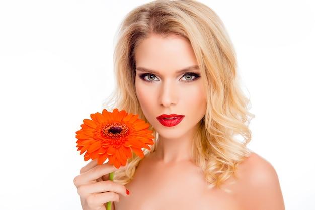 Ritratto di bella giovane donna sorridente con gerbera arancione
