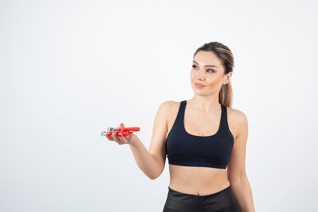 Ritratto di bella donna sportiva con espansore a mano.
