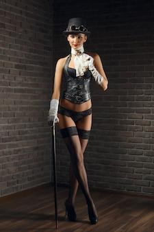 Ritratto di una bella ragazza steampunk in lingerie e calze, cappello e occhiali.