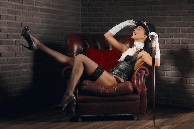 Ritratto di una bella ragazza steampunk in lingerie e calze posa nella vecchia poltrona con le gambe in su.