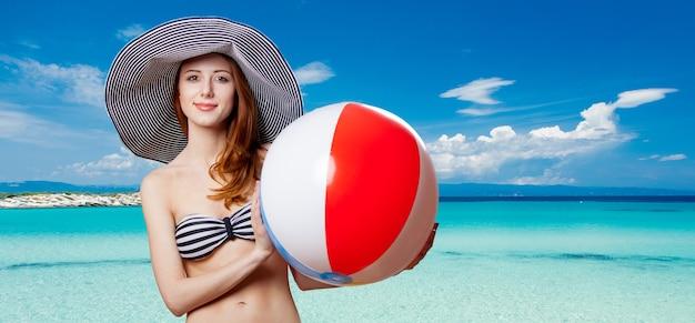 Ritratto di una bella ragazza rossa di stile in bikini con la palla sulla costa tropicale