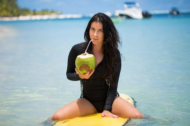 Ritratto di una bella ragazza surfista con cocco verde di palma seduto su tavola da surf longboard surf giallo