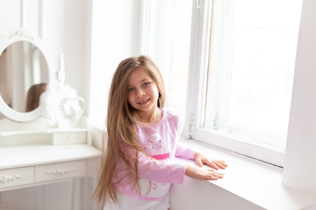 Ritratto di una bella ragazza adolescente sta vicino alla finestra bianca.