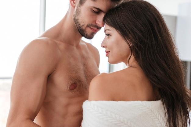 Ritratto di bella giovane coppia tenera innamorata a casa