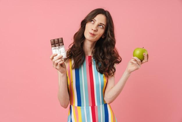Ritratto di bella donna carina pensante in posa isolata sul muro rosa che tiene mela e cioccolato