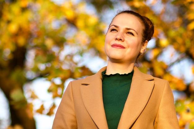 Ritratto di bella giovane donna premurosa nel parco autunno dorato sorridente, sognante, esaminando