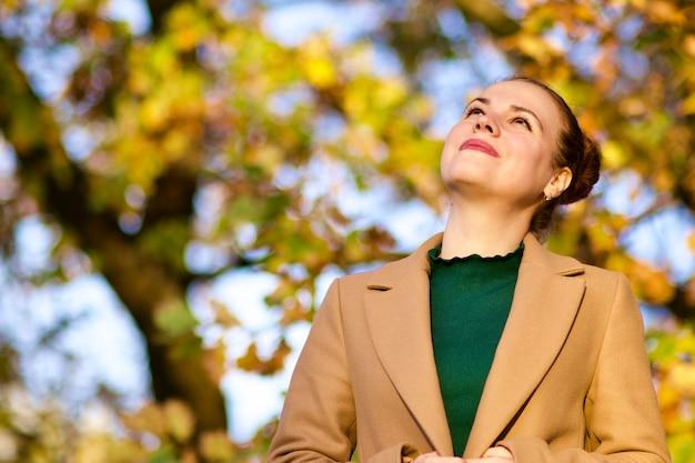 Ritratto di bella giovane donna premurosa nel parco autunno dorato sorridendo, sognando, guardando