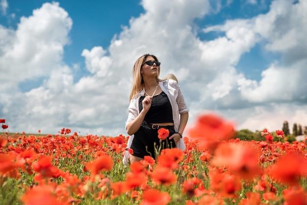 Ritratto di bella donna ucraina con capelli biondi, indossa una camicetta bianca, in posa nel campo di papaveri al giorno pieno di sole, stile di vita