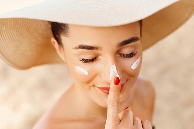 Ritratto di bella donna che applica la crema solare