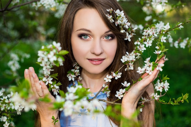 Ritratto di bella donna nel giardino di ciliegio in fiore