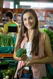 Ritratto dei broccoli d'acquisto della bella donna nella sezione organica