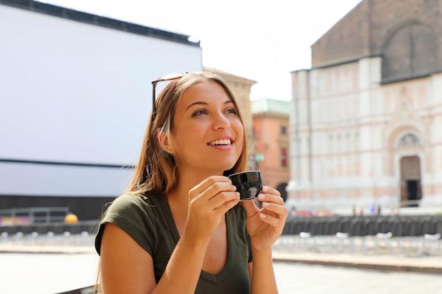 Ritratto di bella donna che beve caffè seduti all'aperto in un caffè italiano godendo il suo viaggio in italia