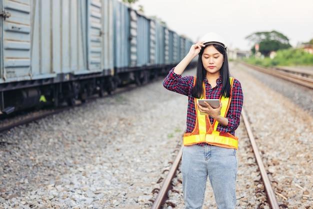 Ritratto di bella donna ingegneria utilizzando tablet con elmetto protettivo davanti al garage del treno.