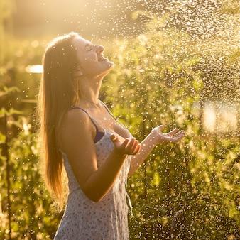 Ritratto di bella donna che gode della pioggia al giorno soleggiato al giardino