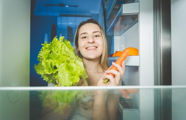 Ritratto di bella donna che tiene carota e insalata fresca