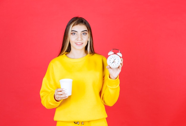 Ritratto di bella donna che tiene tazza e orologio sulla parete rossa