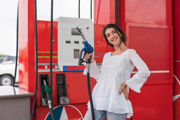 Ritratto di bella donna che tiene l'ugello della pompa del carburante e fa rifornimento di auto self-service nella stazione di servizio