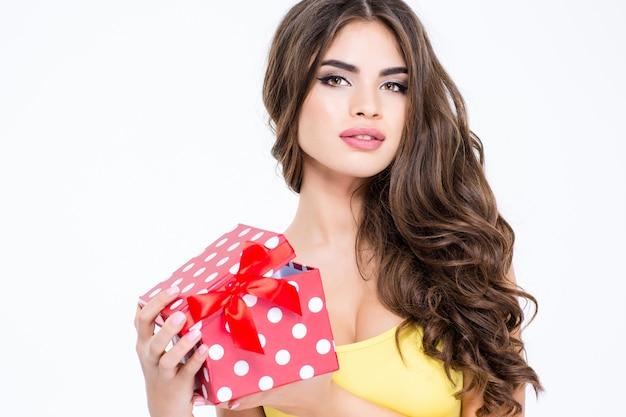 Ritratto di una bella donna che tiene in mano una confezione regalo e guarda la telecamera isolata su uno sfondo bianco