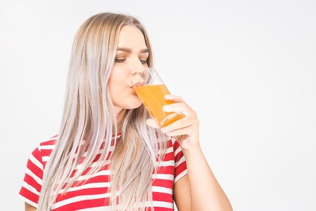 Ritratto di una bella donna che tiene un bicchiere di succo d'arancia