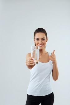 Il ritratto di bella donna tiene il bicchiere d'acqua. bere acqua. ragazza con un bicchiere d'acqua. concetto di dieta