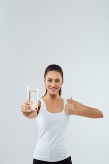 Il ritratto di bella donna tiene il bicchiere d'acqua. bere acqua